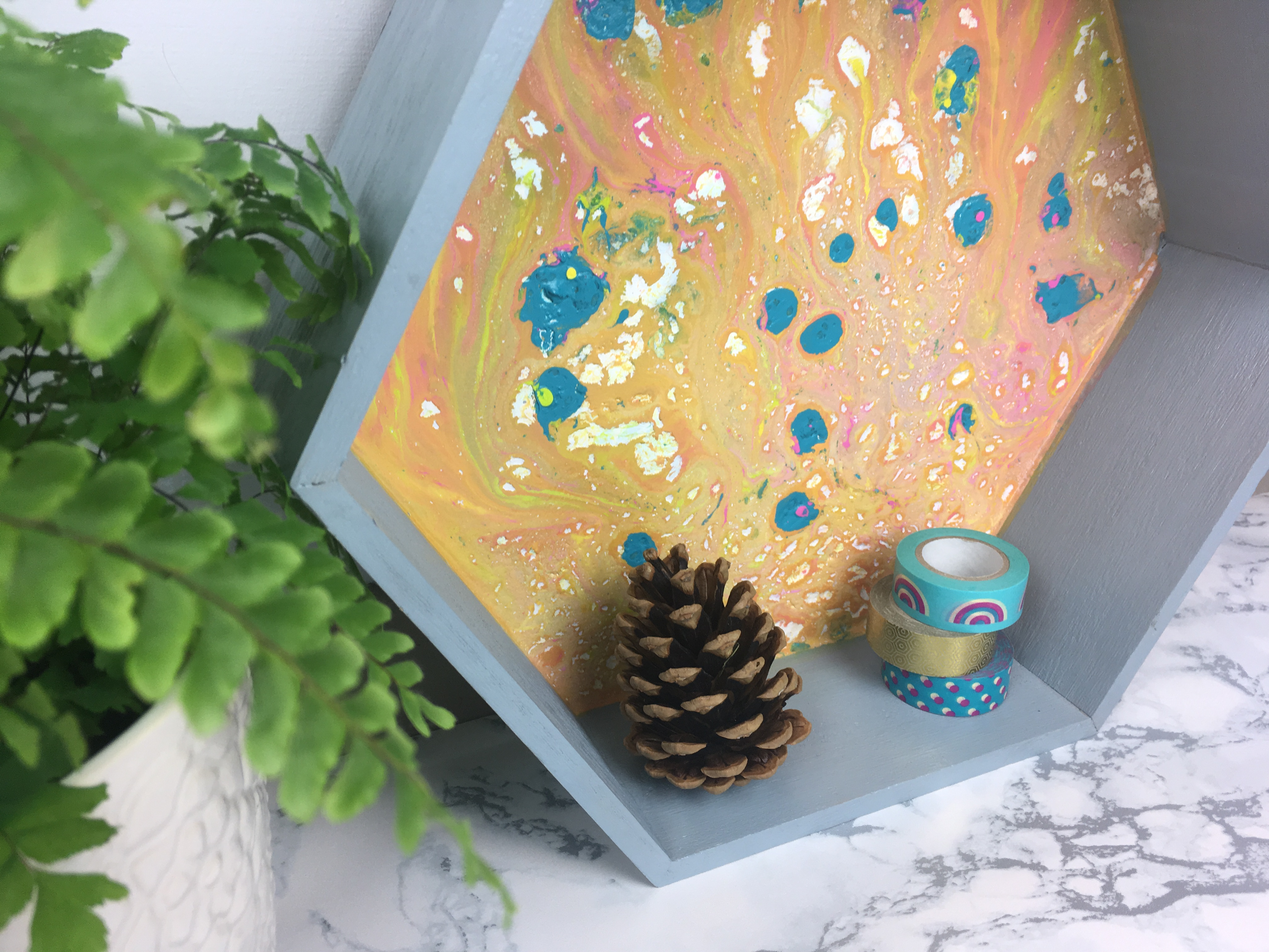 Angled shot of finished shelf with plant, pinecone and washi tape