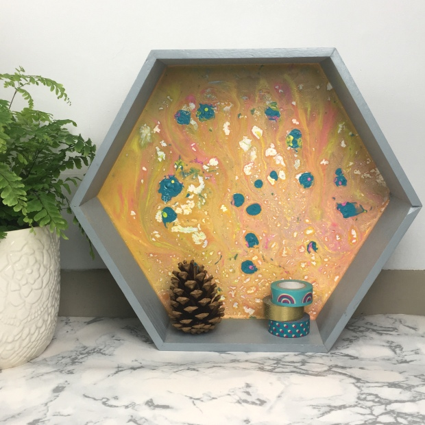 front shot of finished shelf with plant, pinecone and washi tape