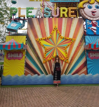 girl standing in front of striped star at dreamland margate