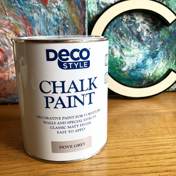 tin of Aldi chalk paint on wooden surface with art work behind