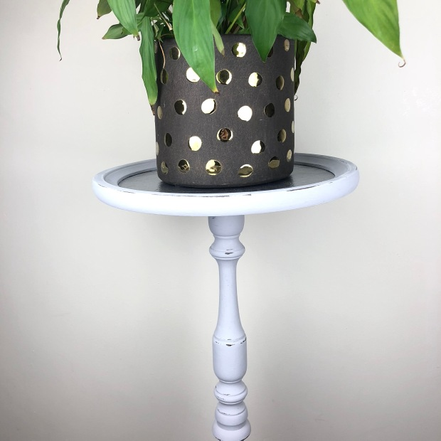 dark grey plant pot with metallic gold polkas sat on a tall grey plant stand