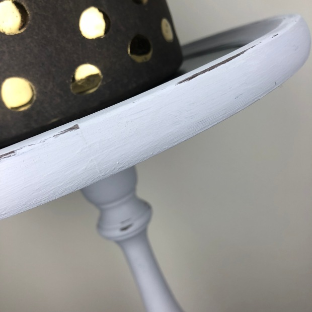 close up of light grey plant stand with dark grey plant pot stand on top