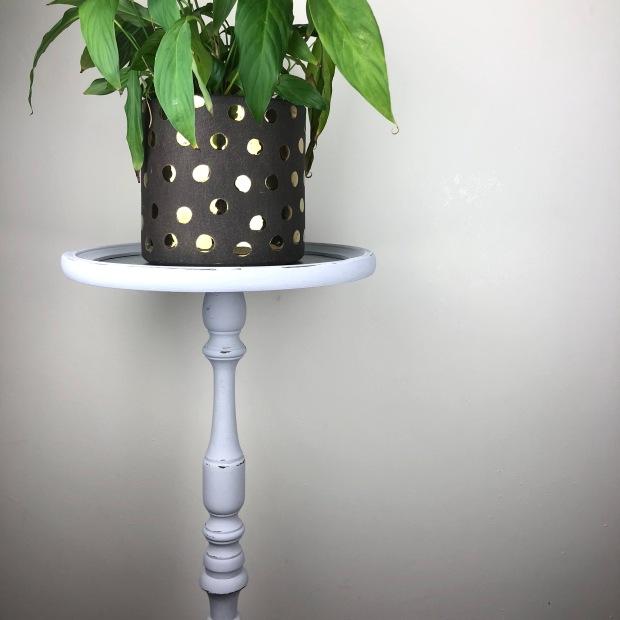 dark grey plant pot with metallic gold polkas sat on a tall grey plant stand