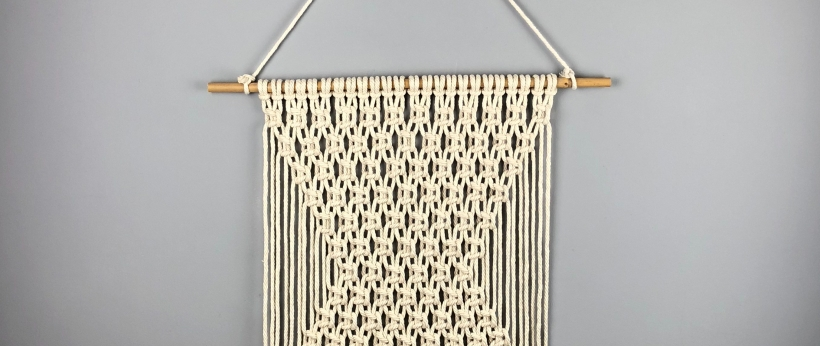 Macramé wall hanging on grey wall