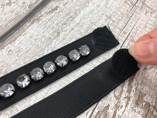 Ladies hand sticking velcro dot onto black elastic