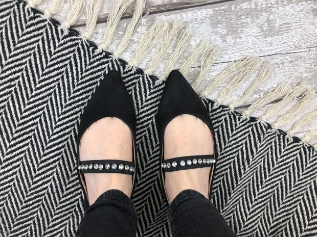 ladies feet wearing black jewelled pumps on monochrome rug