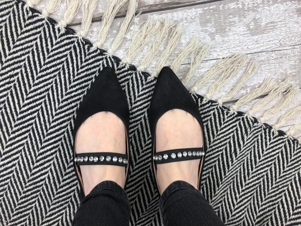ladies feet wearing black jewelled pumps on monochrome rug