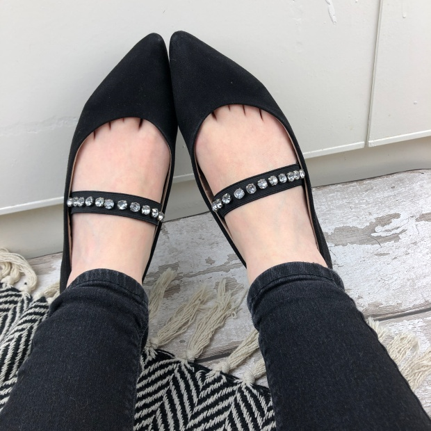 black shoes on feet with jewelled cross bar