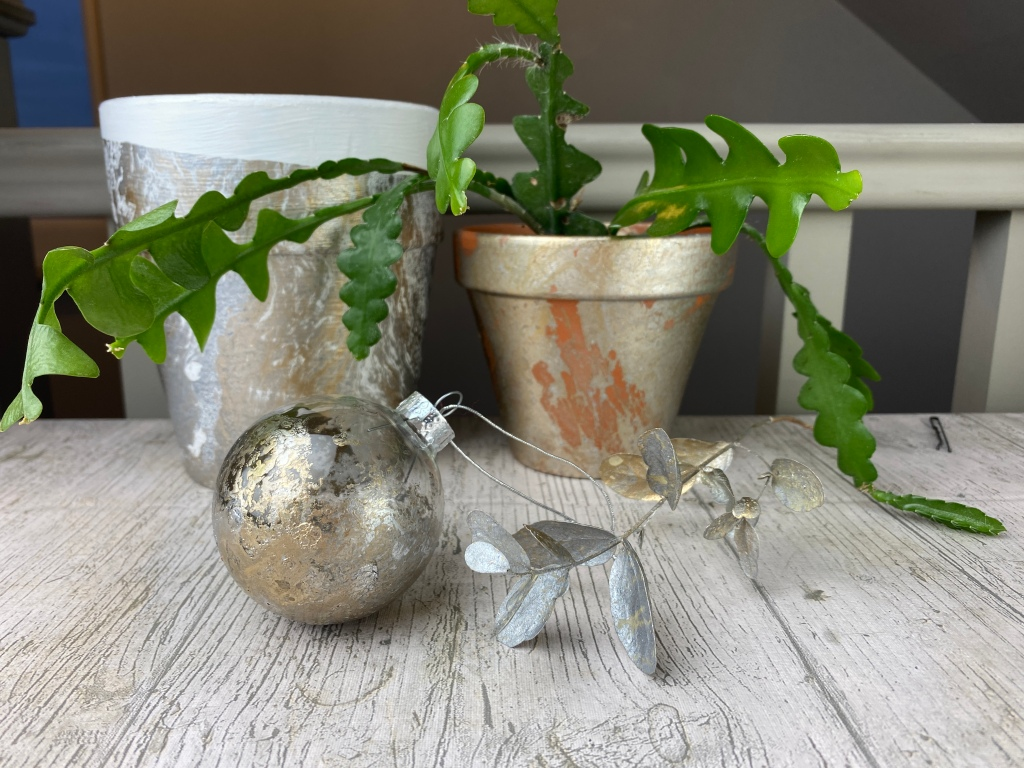 Picture of a desk with two plant pots, Christmas bauble and eucalyptus. All have been hydro dipped in gold and silver paint.